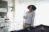 Portrait of smiling woman playing pool - HEROF24319