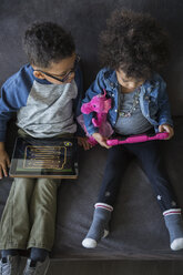 Overhead of brother and sister using digital tablets - HEROF24337