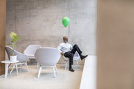 Mature businessman with green balloon sitting on armchair using digital tablet - FMKF05354