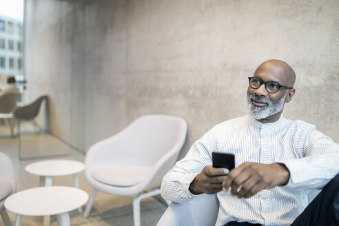 Portrait of smiling mature businessman with smartphone - FMKF05357