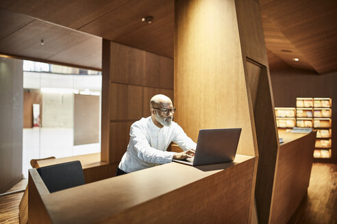 Mature man working on laptop at workspace in library - FMKF05360