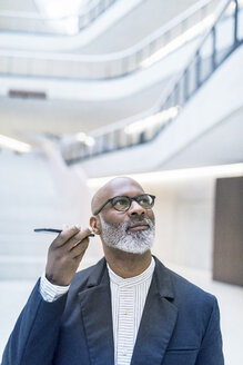 Portrait of mature businessman using smartphone - FMKF05369