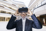 Portrait of bearded mature businessman with Virtual Reality Glasses - FMKF05372