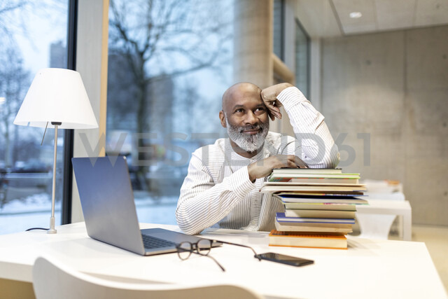 Portrait of smiling mature man sitting at desk with laptop and stack of books - FMKF05378 - Jo Kirchherr/Westend61