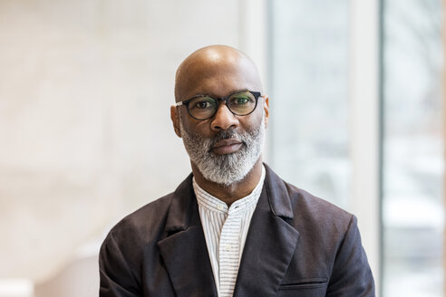 Portrait of bald mature businessman with grey beard wearing glasses - FMKF05390