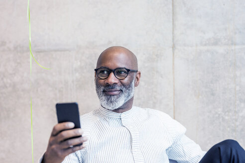 Portrait of smiling mature businessman with smartphone - FMKF05393