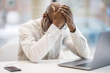 Mature businessman with earphones, smartphoen and laptop sitting with hands on head at desk - FMKF05396