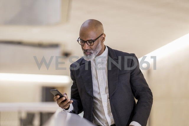 Portrait of bald mature businessman looking at cell phone - FMKF05399 - Jo Kirchherr/Westend61