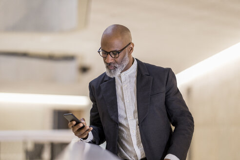 Portrait of bald mature businessman looking at cell phone - FMKF05399