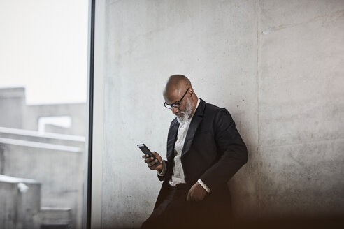 Bald mature businessman leaning against concrete wall looking at cell phone - FMKF05405