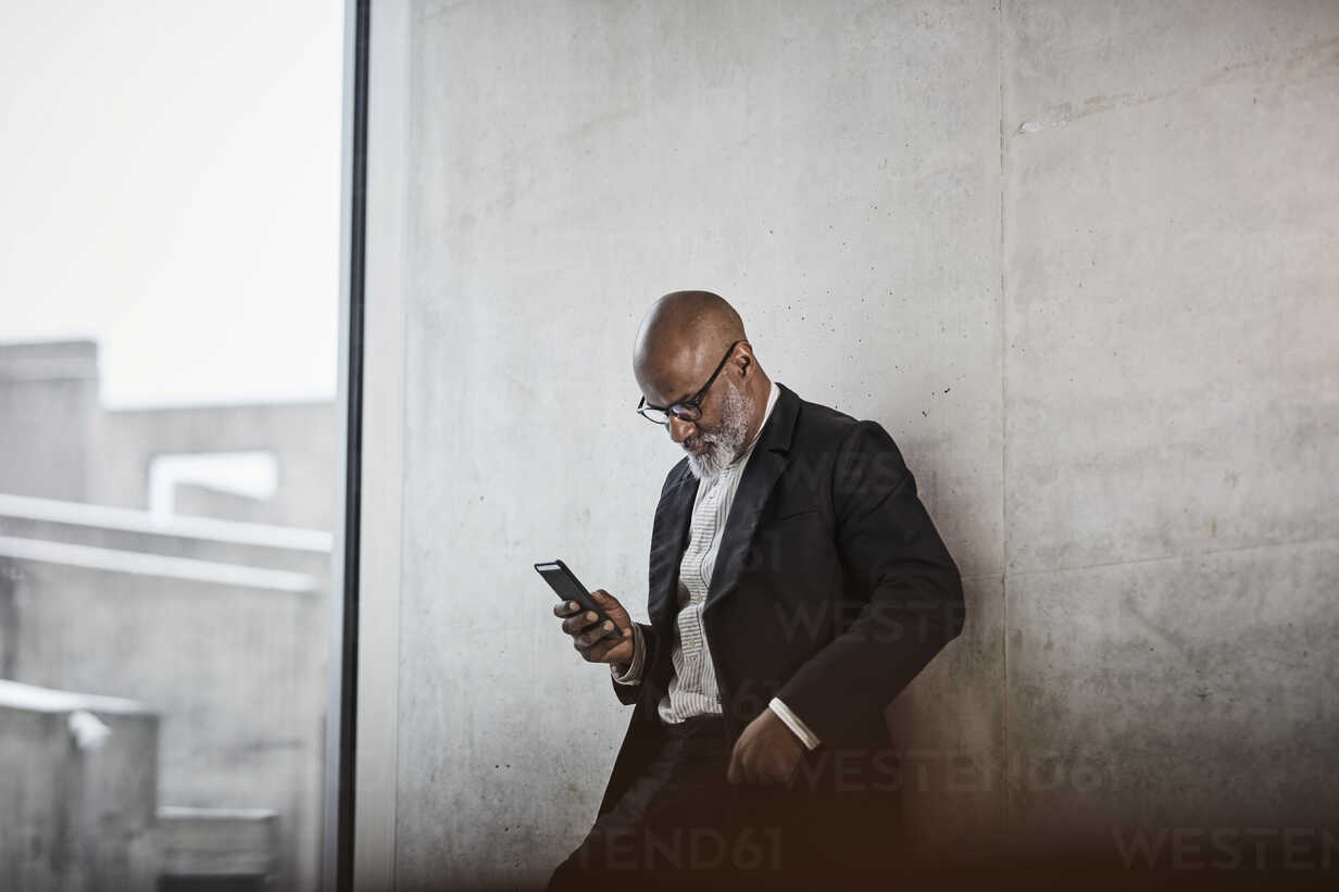Bald mature businessman leaning against concrete wall looking at cell phone - FMKF05405 - Jo Kirchherr/Westend61