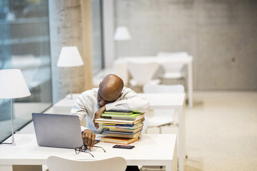 Exhausted mature man sitting at desk leaning on stack of books - FMKF05408
