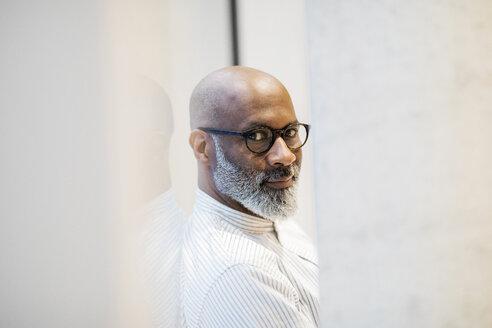 Portrait of bald mature businessman with grey beard wearing glasses - FMKF05411
