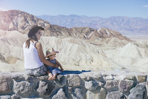 USA, California, Death Valley National Park, Twenty Mule Team Canyon, mother and baby girl sitting on wall - GEMF02848