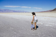 USA, California, Death Valley National Park, Badwater Basin, mother and baby girl walking in salt basin - GEMF02854