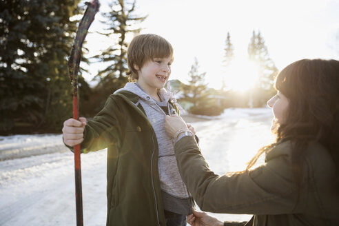 Mother adjusting sweatshirt of son holding ice hockey stick on snowy road - HEROF24366