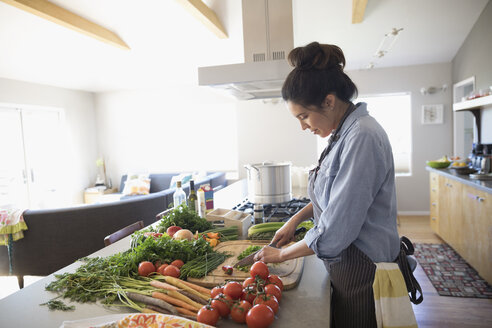 Latina woman cutting vegetables in kitchen - HEROF24486