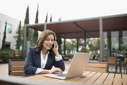 Latina businesswoman using laptop and talking on cell phone on office patio - HEROF24495