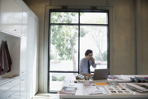 Male designer working at laptop and talking on cell phone in conference room - HEROF24498