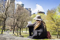 Rear view of woman reading book while sitting on rock at Central Park - ASTF02864