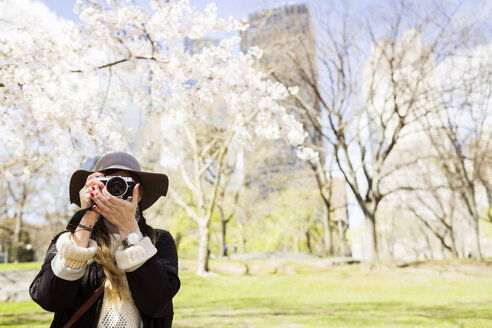 Front view of woman with camera standing at Central Park - ASTF02867
