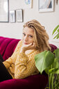 Portrait of beautiful woman sitting on sofa at home - ASTF02888