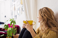 Woman holding coffee cup while sitting against wall - ASTF02894