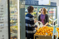 Young woman and man talking while buying oranges in supermarket - ASTF03209