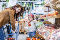 Girl holding tomatoes while standing by mother in supermarket - ASTF03215