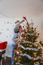 Father and daughter decorating Christmas tree at home - ASTF03251