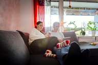 Couple using tablet and smart phone while relaxing on sofa at home - ASTF03254