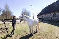 Woman standing with white horse on field during sunny day - ASTF03353