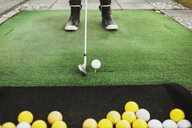 Low section of woman aiming golf ball at driving range - ASTF03380