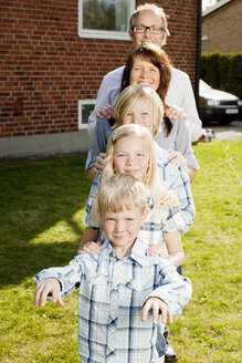 Portrait of family standing in row against house - ASTF03434