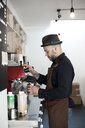 Side view of mid adult barista preparing coffee in cafeteria - ASTF03647