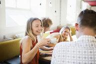 Cheerful friends enjoying coffee in shop - ASTF03749