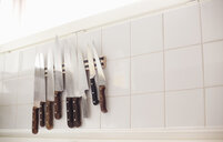 Low angle view of various knives on tiled wall in restaurant kitchen - ASTF03824