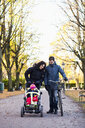 Parents looking at girl on baby carriage in park - ASTF03881