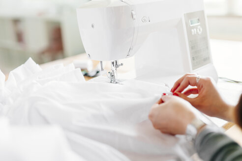 Cropped hands of fashion designer stitching white fabric sewing machine - ASTF03887
