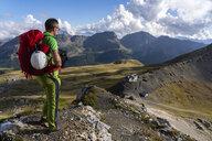 Italy, Veneto, Dolomites, San Pellegrino Pass, mountaineer standing near Paradiso mountain hut - LOMF00806