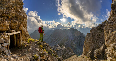 Italy, Veneto, Dolomites, Alta Via Bepi Zac, mountaineer standing on Costabella mountain at sunset - LOMF00815