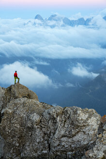 Italy, Veneto, Dolomites, Alta Via Bepi Zac, mountaineer standing on Pale di San Martino mountain at sunset - LOMF00827