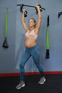 Smiling pregnant woman practicing with kettlebells in a gym - ECPF00522