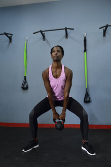 Woman practicing with kettlebell in a gym - ECPF00531