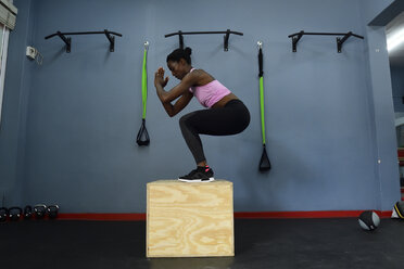 Woman practicing in a gym doing a box jump - ECPF00534