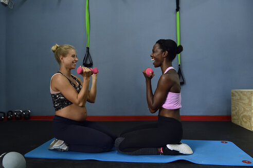 Two happy women doing fitness exercises with dumbbells in a gym - ECPF00543