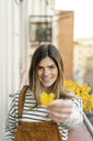 Portrait of smiling young woman on balcony gifting yellow blossom - AFVF02392
