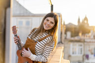 Portrait of smiling young woman standing on roof terrace in the evening playing ukulele - AFVF02401