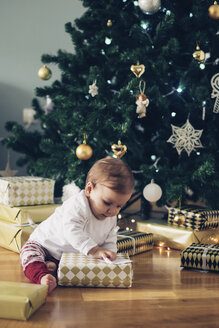 Baby girl sitting on the floor unpacking Christmas gifts - MOMF00629