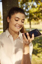 Smiling young woman using smartphone in a park - JHAF00036